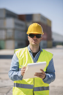 Portrait of a worker with a notepad near cargo containers on industrial site - AHSF00183