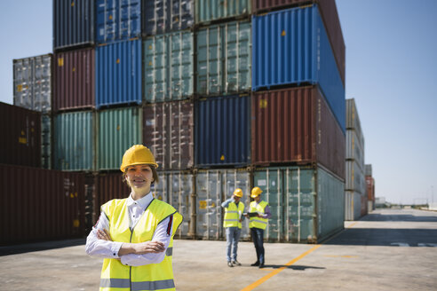 Portrait of confident female worker in front of colleagues and cargo containers on industrial site - AHSF00189
