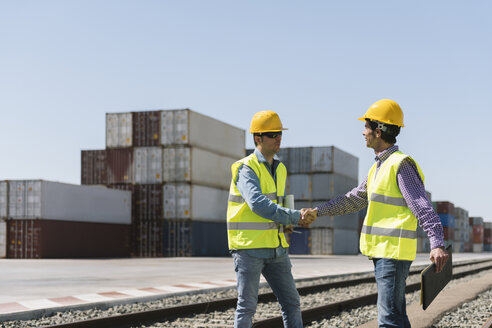 Workers shaking hands on railway tracks near cargo containers on industrial site - AHSF00201