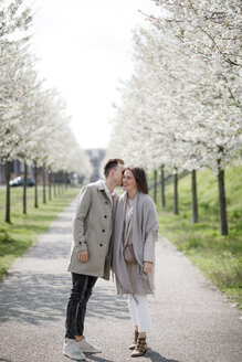 Affectionate couple strolling in a park in spring - KMKF00873