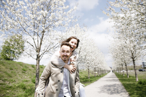 Affectionate couple having fun in a park in spring - KMKF00885