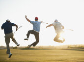 Excited golfers jumping in mid-air on golf course - BLEF00134