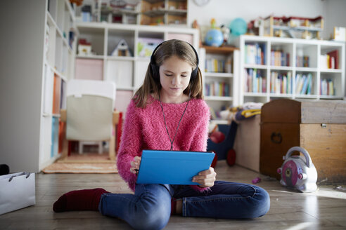 Young girl using digital tablet with headphones, sitting on the floor - RBF07016