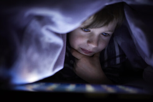 Little boy playing secretly with his digital tablet, hidden under blanket - RBF07028