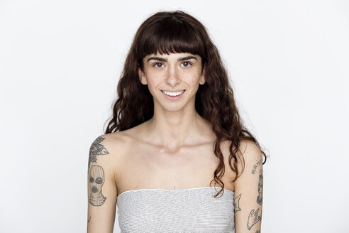 Portrait of smiling young woman with freckles and tattoos on her upper arms - FLLF00119
