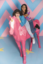 Two happy young women at an indoor theme park with a unicorn figure - AFVF02805