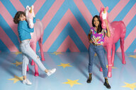 Two happy young women at an indoor theme park with unicorn figures - AFVF02808