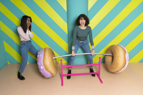 Two happy young women at an indoor theme park having fun with oversized donuts - AFVF02814