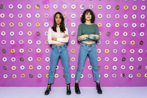 Two young women posing at an indoor theme park with donuts at the wall - AFVF02817