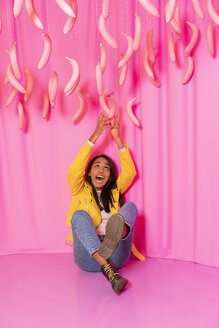 Young woman screaming at an indoor theme park with dangling pink bananas - AFVF02823