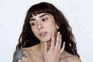 Portrait of tattooed young woman with freckles - FLLF00122
