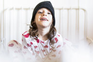 Portrait of smiling little girl sitting in bed wearing cap and pyjama - ERRF01189