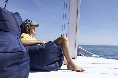 Indonesia, Komodo National Park, girl sitting in beanbag on a sailing boat - MCF00124