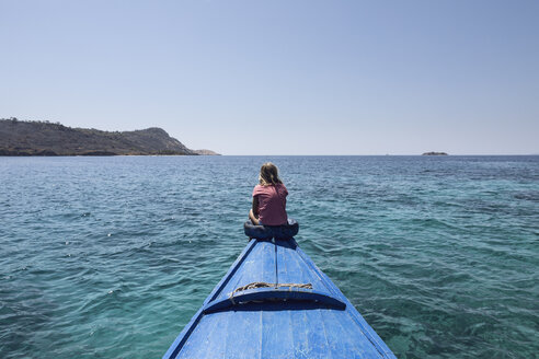 Indonesia, Komodo National Park, girl sitting on bow of a boat - MCF00139