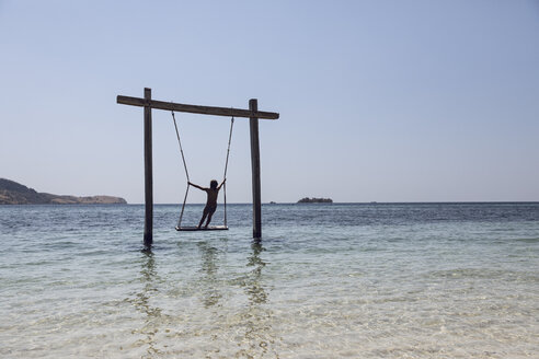 Indonesia, Komodo National Park, girl on a swing in the sea - MCF00148