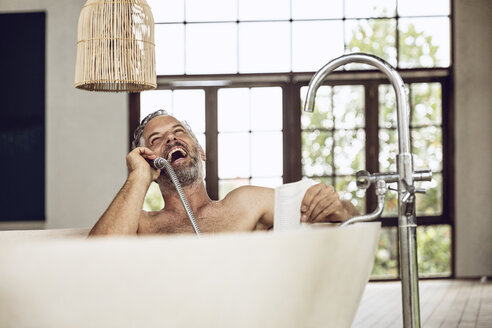 Laughing man in bathtub using shower head as telephone receiver - MCF00160