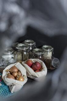 Zwiebeln und Äpfel in Stoffbeuteln aus Baumwolle, Einkaufen ohne Plastik, Müll vermeiden, Lebensmittel in Gläsern dahinter, durch eine Plastiktüte fotografiert, Studio - STBF00294