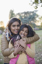 Portrait happy Muslim mother in hijab hugging daughter in park - CAIF23200