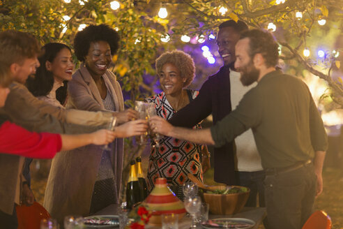 Happy friends toasting wine glasses at dinner garden party - CAIF23206