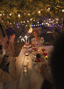 Happy friends celebrating birthday with sparkler cake at garden party table - CAIF23224