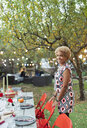 Portrait happy woman hosting dinner garden party - CAIF23230