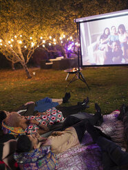 Friends relaxing, watching movie on projection screen in backyard - CAIF23233