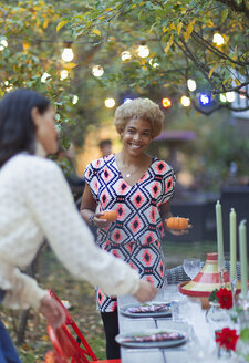 Happy women friends setting table for dinner garden party - CAIF23245