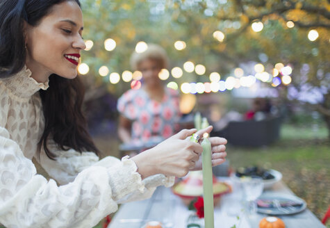Woman lighting candles for dinner garden party - CAIF23248
