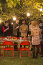 Friends talking under trees at dinner garden party - CAIF23251