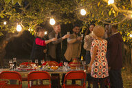 Friends celebrating, toasting champagne at dinner garden party - CAIF23257