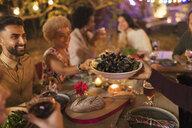 Friends passing mussels, enjoying dinner garden party - CAIF23269