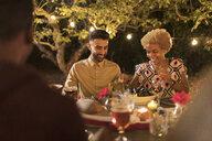 Couple enjoying dinner garden party - CAIF23272