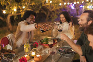 Friends pouring and drinking wine, enjoying dinner garden party - CAIF23275