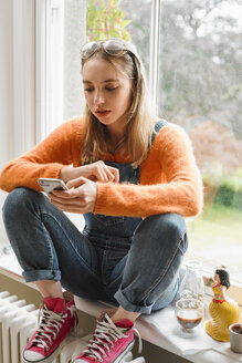 Young woman texting with smart phone in window - CAIF23311