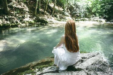 Caucasian woman sitting near river - BLEF00195