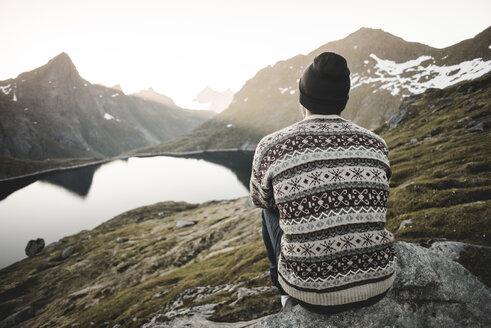 Caucasian man sitting on rock admiring scenic view of mountain lake - BLEF00198
