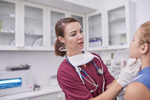Female pediatrician examining girl in clinic examination room - CAIF23360