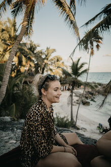 Mexico, Quintana Roo, Tulum, portrait of smiling young woman relaxing on the beach - LHPF00666