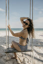 Mexico, Quintana Roo, Tulum, happy young woman on a swing on the beach - LHPF00678