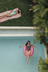 Two young women relaxing at swimming pool - LHPF00690
