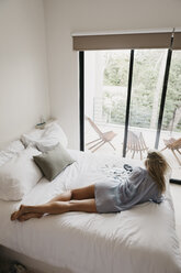 Young woman lying in bed with photographs - LHPF00693