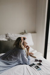 Young woman lying in bed with book, sunglasses and polaroid pictures - LHPF00696