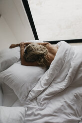 Blond young woman lying in bed - LHPF00699