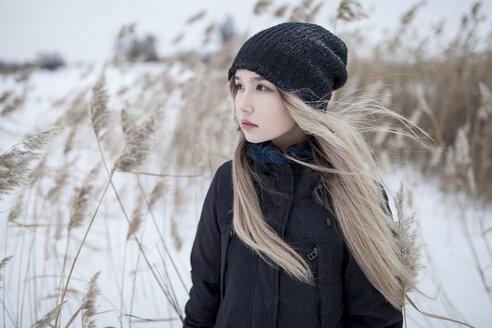 Wind blowing hair of Asian teenage girl in winter - BLEF00270