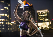 Caucasian woman spraying water on face in city at night - BLEF00288