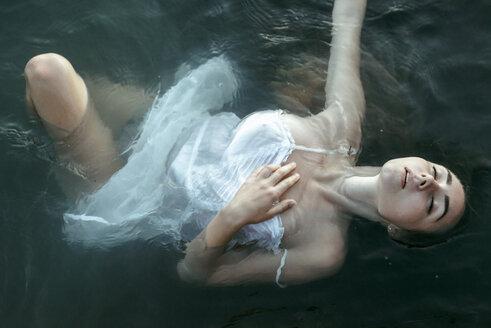 Caucasian woman wearing a dress floating in water - BLEF00396