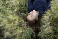 Pensive Caucasian girl laying in field - BLEF00453