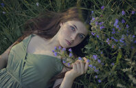 Caucasian woman laying in grass with wildflowers - BLEF00483