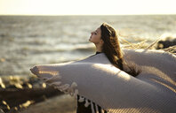 Wind blowing shawl of Caucasian woman at beach - BLEF00492