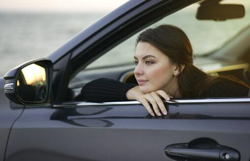 Pensive Caucasian woman leaning in car window - BLEF00495